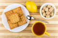 Biscuits in plate, cup of tea, bowl of lumpy sugar Royalty Free Stock Photo