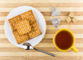 Biscuits sandwiches, cup of tea, lumpy sugar on striped table Royalty Free Stock Photo