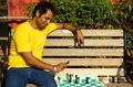 The bishop move is best a young man playing a chess on a park bench lifting a black Stock Photo