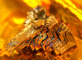 Bismuth crystal a multicolored warm illuminated in golden back Royalty Free Stock Images