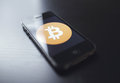 Bitcoin technology the new digital cryptocurrency sweeping across the world being utilized on a smartphone Royalty Free Stock Image