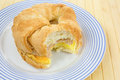 Bitten croissant breakfast sandwich on plate a with sausage egg and cheese a blue striped Royalty Free Stock Images