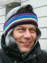 Bitter cold portrait of a smiling man in winter clothing with scarf and headband on his head Stock Photography