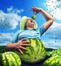 Bizarre farmer with watermelon instead of the abdomen on field in summer Stock Photo