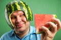 Bizarre man in a helmet from a watermelon preparing to eat Royalty Free Stock Image