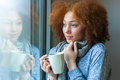 Black african american teenage girl drinking a hot beverage and looking through window Stock Image