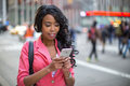 Black african american woman texting cellphone in city ny Stock Images
