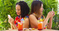 Black and asian best friends on vacation using mobile phones outdoors Stock Photo