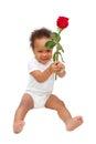 Black baby presenting flower rose. Royalty Free Stock Photo