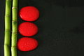 Black background with bamboo branch on the left and red zen pebbles with drops of water