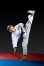 On a black background and red mat the boy beat blow leg mawashi gerimawashi geri athlete in performing in white karategi on a bla Stock Photo