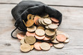 Black bag and coin on wood background Stock Image