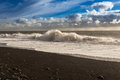 Black beach, big waves, blue dramatic sky with clouds Royalty Free Stock Photo