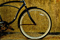 Black bicycle frame with flat tire photographed against a concrete wall Royalty Free Stock Photos