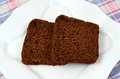 Black bread two slices of on a white plate Royalty Free Stock Images