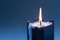 Black candle with burning wick on dark blue gradient background. copy space Royalty Free Stock Photo