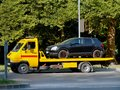 Image : Black car is loaded on a yellow car tow truck on a city street ca towing