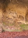 Black carbon paint of human hunting on sandstone wall, copy of prehistoric picture. Abstract children art in cave