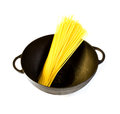 Black cast iron pot with raw pasta isolated on a white background Royalty Free Stock Photos