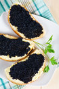 Black caviar on a slice of bread and butter Royalty Free Stock Image
