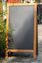 Black chalkboard stand on wood for a restaurant menu in the street
