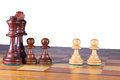 A black chessfamily fighting against two white pawns king queen and versus Stock Photography