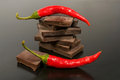 Black chocolate with red hot pepper on a dark background Royalty Free Stock Photos