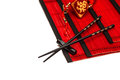 Black chopsticks on red bamboo mat chinese new year ornament asian style table place setting with lucky charm Royalty Free Stock Photography