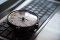 Black clock lay on keyboard time metaphor concept in dark low ke Royalty Free Stock Photo
