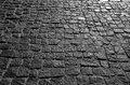 Black cobbled stone road background with reflection of light seen on the road. Black or dark grey stone pavement texture. Royalty Free Stock Photo