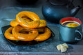 Black coffee cup with bagels on a black bowl and three pieces of sugar on a blue background Royalty Free Stock Photo