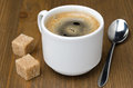 Black coffee with foam sugar cane cubes and spoon on a wooden table close up Stock Photos