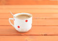 Black coffee white cup with red dots full of with spoon lying on wooden table Royalty Free Stock Images
