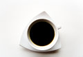 Black coffee in a white cup on a white saucer.