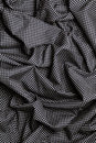 Black cotton fabric with white dots design texture. Overlapping strips. Background.