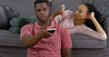Black couple relaxing at home with their gadgets young watching tv and using smartphone Royalty Free Stock Photo