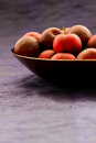 Black Diamond plums in a copper bowl against a blue silk background with copy space. Royalty Free Stock Photo