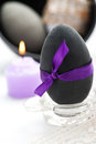 Black easter egg with bow purple and candle Stock Photography