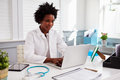Black female doctor wearing white coat at work in an office Royalty Free Stock Photo
