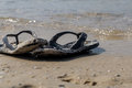 black flip flops on the beach, summer vacations Royalty Free Stock Photo