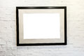 Black frame with blank space on brick wall square inside white gallery or house interior presentation or exhibition of photos Royalty Free Stock Photo