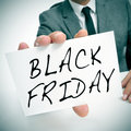 Black friday a man wearing a suit holding a signboard with the words written in it Stock Photo