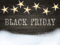 Black Friday sign on wooden background with star-shaped lights and snow. Design template for banners, flyers and so.