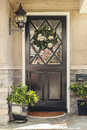 Black front door to home with flower wreath a a an ornate and classic light fixture also seen are plants and a stone porch Royalty Free Stock Photo