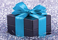 A black gift with a blue ribbon and a bow Royalty Free Stock Photo