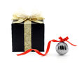 black gift box with golden ribbon and shining net bow and metallic glossy gray christmas ball with red ribbon bow isolated on whit Royalty Free Stock Photo