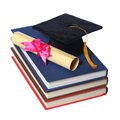 Black graduation cap with degree on books isolated on white background Royalty Free Stock Photography