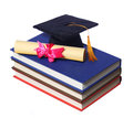 Black graduation cap with degree on books isolated white background Stock Photos