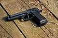 Black gun mm on a wooden floor Royalty Free Stock Image