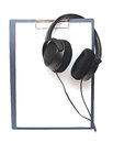 Black headphone a and blank clipboard close up Royalty Free Stock Photo